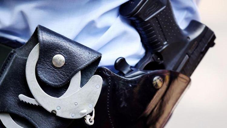 Ein Polizist mit Handschellen und Pistole am Gürtel. Foto:Oliver Berg/Archivbild