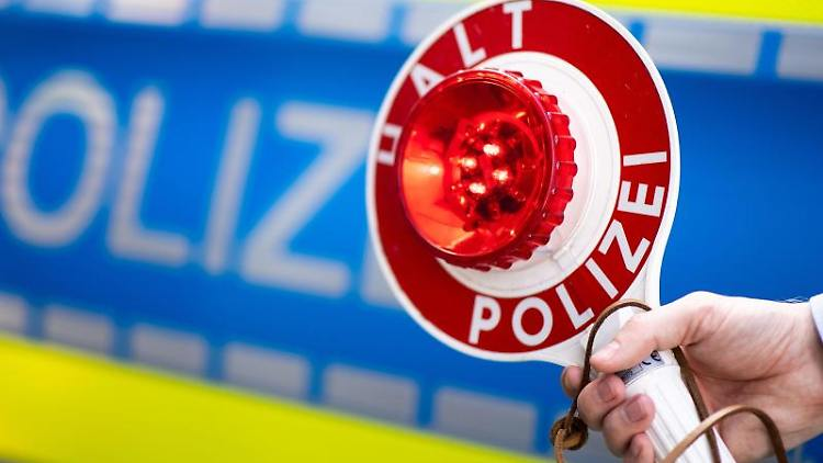 Ein Polizist bittet um Anhalten. Foto: Marius Becker/Archivbild