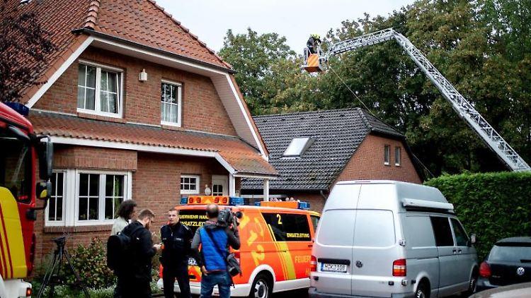 Einsatzkräfte der Feuerwehr bergen die Leiche aus dem Obergeschoss des Mehrfamilienhauses in Hannover-Ahlem. Foto: Hauke-Christian Dittrich