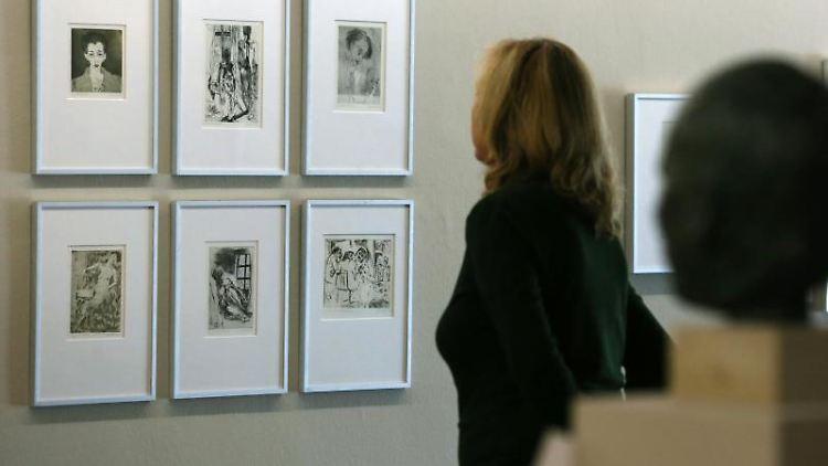 Eine Frau schaut sich in der Rostocker Kunsthalle Grafiken von Inge Jastram an. Foto: Bernd Wüstneck/Archivbild