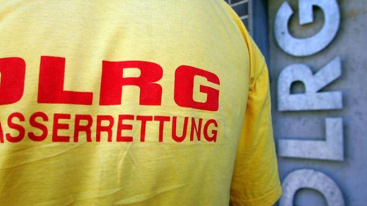Ein Helfer der DLRG steht vor einem Logo der DLRG. Foto: Patrick Seeger/Archivbild