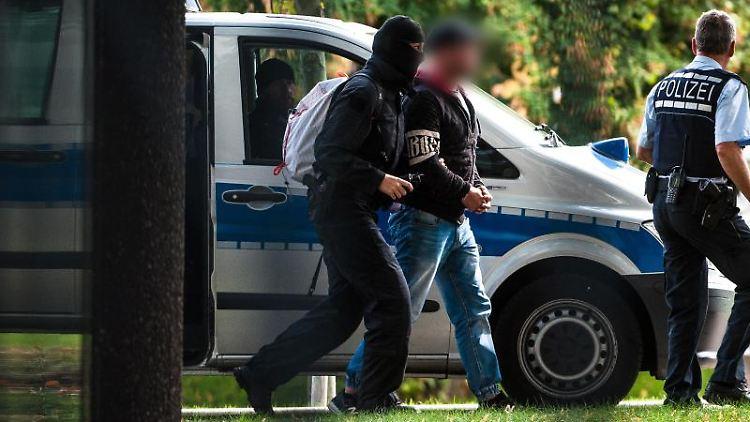 Einer der Rechtsterroristen, die in Bayern und Sachsen festgenommen wurden wird von Polizisten abgeführt. Foto:Christoph Schmidt/Archivbild