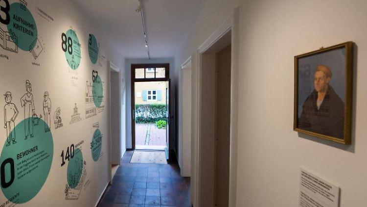In der Fuggerei hängt ein Porträt von Jakob Fugger gegenüber einer Wand, auf der Zahlen und Fakten aufgemalt sind. Foto:Stefan Puchner