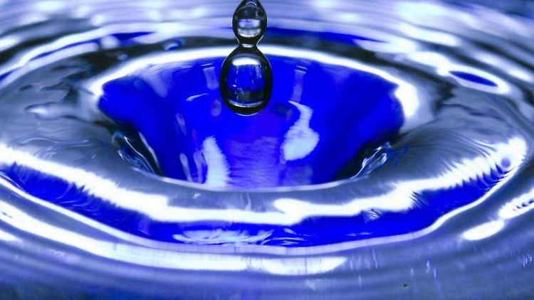 Ein Wassertropfen fällt in eine blaue Wasserschüssel. Foto: Jens Büttner/Archiv