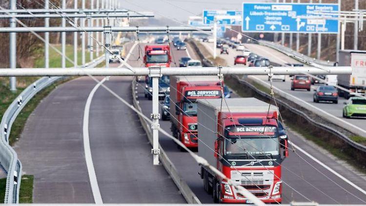 Lastwagen fahren am neu installierten Oberleitungssystem vorbei. Foto: Markus Scholz/Archivbild