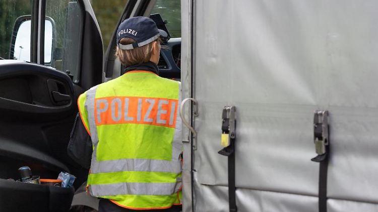 Eine Polizistin kontrolliert am Rastplatz einen Transporter. Foto: Robert Michael/Archivbild