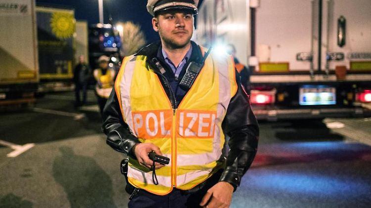Ein Polizist steht bei der Kontrolle von LKW-Fahrern auf einem Rastplatz. Foto: Andreas Arnold/Archivbild