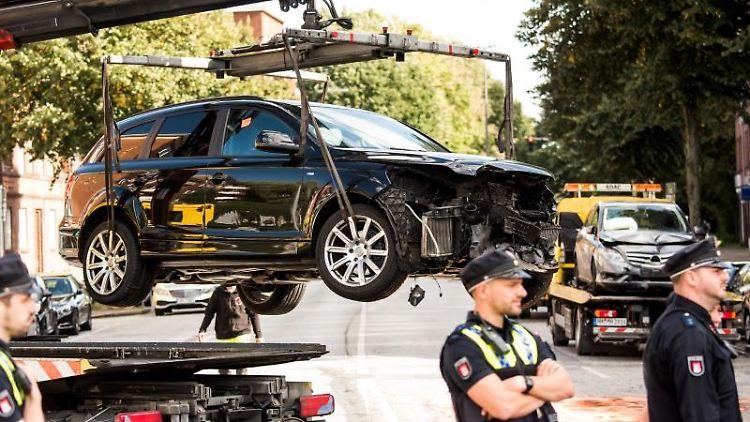 Polizisten stehen auf einer Straße im Stadtteil Horn, auf der ein beschädigtes Auto abtransportiert wird. Foto: Daniel Bockwoldt/Archivbild