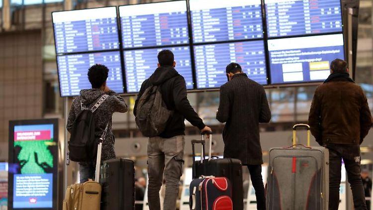 Fluggäste stehen vor einer Anzeigetafel im Terminal 1 des Flughafens in Hamburg. Foto:Christian Charisius/Archivbild