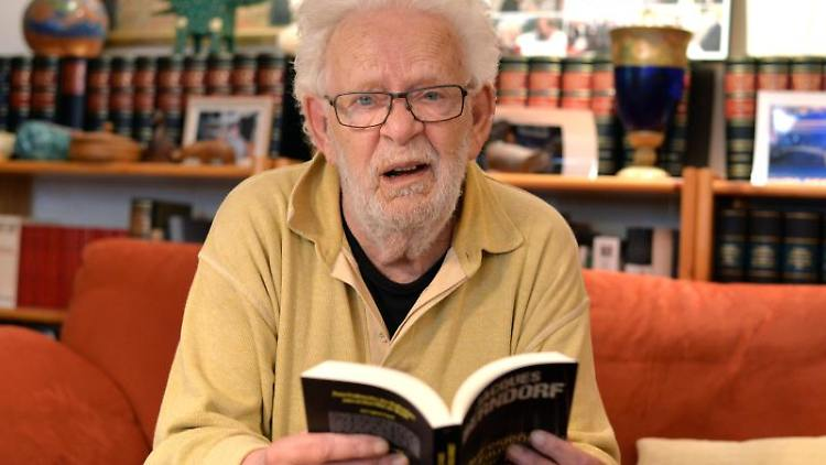 Krimiautor Jacques Berndorf alias Michael Preute blättert in seinem Haus in einem Buch. Foto:Harald Tittel/Archiv