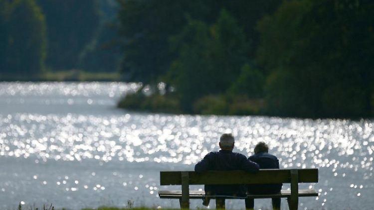 Ein Pärchen auf einer Sitzbank ist durch die glitzernde Wasseroberfläche als Silhouette zu erkennen. Foto: Nicolas Armer