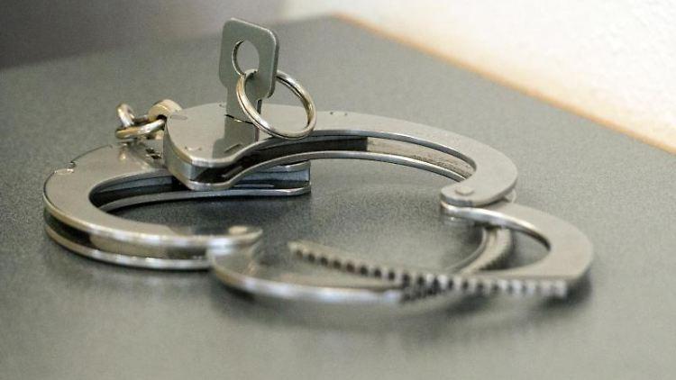 Handschellen liegen auf einem Tisch. Foto: Armin Weigel/Archivbild