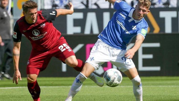 Oliver Sorg aus Nürnberg und der Darmstädter Tim Skarke (l-r.) im Zweikampf um den Ball. Foto: Hasan Bratic
