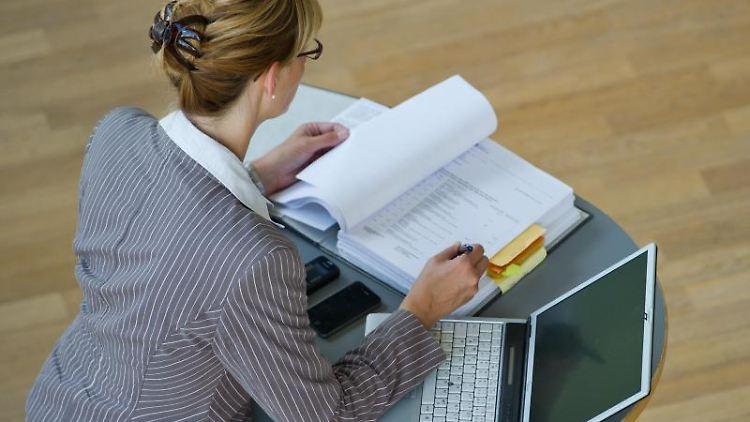 Eine Geschäftsfrau mit Aktenordner und Laptop. Foto: Patrick Pleul/Archivbild