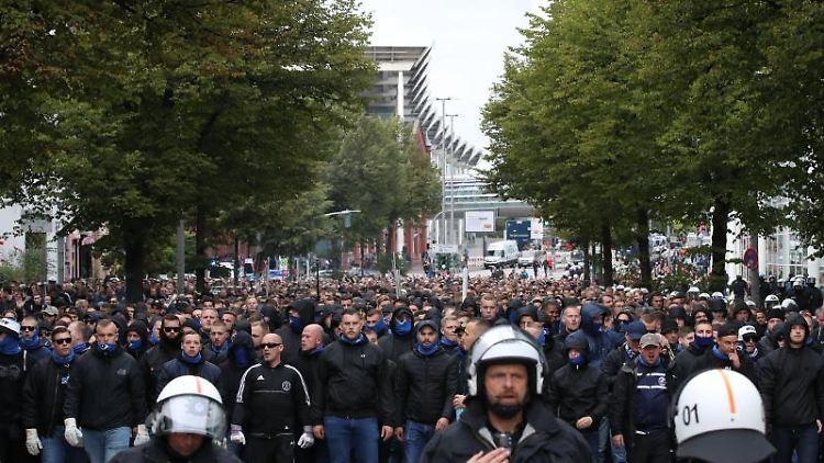 HSV-Anhänger werden von der Polizei beim Fan-Marsch zum Derby beim FC St. Pauli geleitet. Foto: Christian Charisius