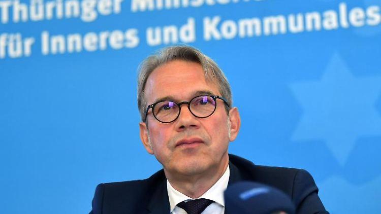 Georg Maier (SPD), Innenminister von Thüringen, sitzt bei einer Pressekonferenz. Foto: Martin Schutt/Archivbild