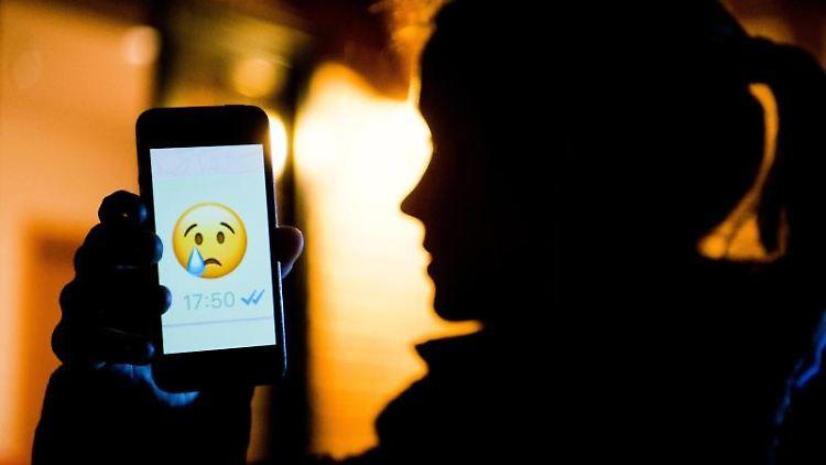 Ein junges Mädchen zeigt das Display eines Smartphones mit einem weinenden Emoji. Foto: Julian Stratenschulte/Archivbild
