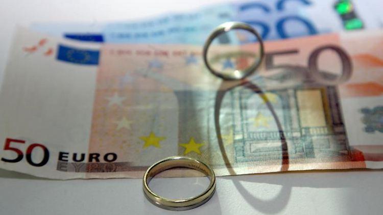 Zwei Eheringe liegen auf Geldscheinen.Foto: Stephanie Pilick/Archivbild