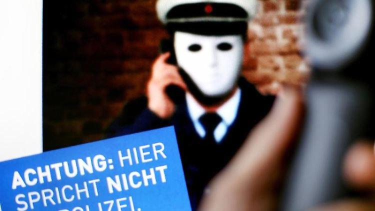 Ein Telefonhörer vor einem Polizeiplakat mit der Aufschrift