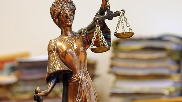Eine goldfarbene Justitia-Figur steht vor Aktenbergen. Foto: Britta Pedersen/Archivbild
