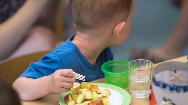 Ein Kind isst in einer Kita Apfelstücke. Foto: Andreas Arnold/Archivbild