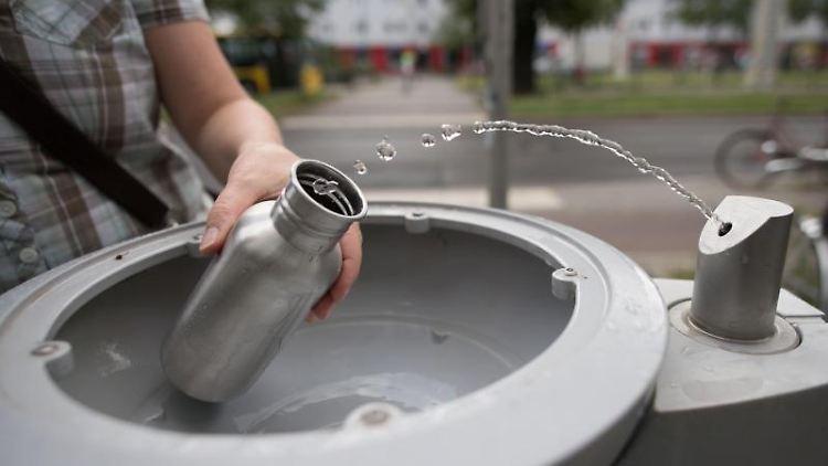 An einem Wasserspender der Berliner Wasserbetriebe füllt sich ein Passant seine Trinkflasche mit Wasser auf.Foto:Jörg Carstensen/Archivbild