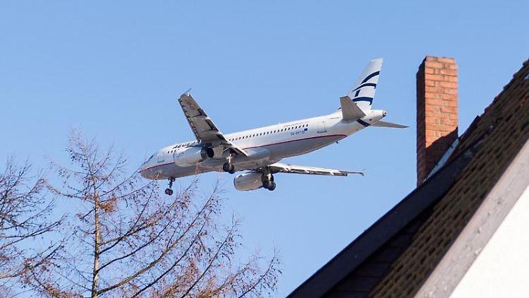 Fluglärm: Ein Flugzeug befindet sich über einem Wohnhaus im Stadtteil Niendorf im Landeanflug auf den Flughafen. Foto: Daniel Bockwoldt/Archiv