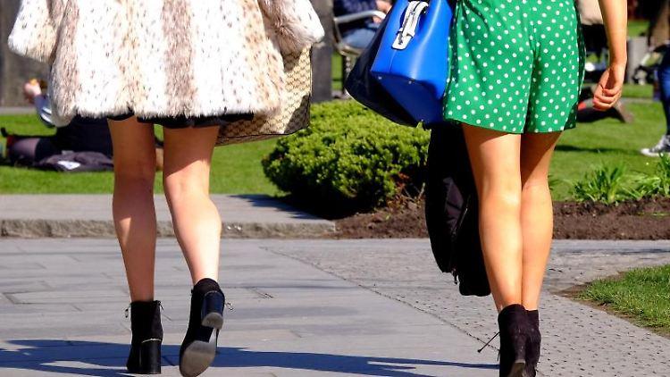 Zwei Frauen in kurzen Röcken gehen auf einem Weg. Foto: Jane Barlow/PA Wire/Archivbild