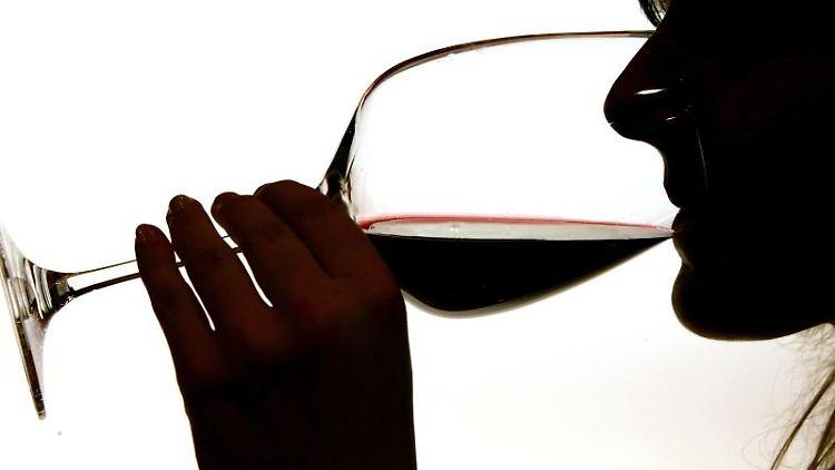 Eine Frau trinkt aus einem Rotweinglas. Foto: Gero Breloer/Archivbild