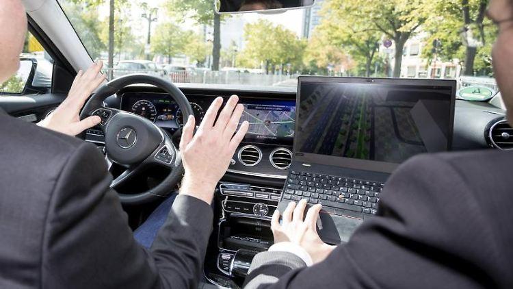 Zwei Männer fahren bei einer Veranstaltung zur Eröffnung eines Testfelds für automatisiertes Fahren in Berlin. Foto: Christoph Soeder