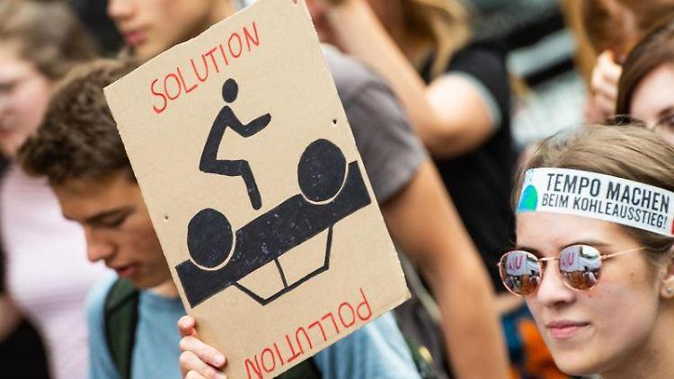 Eine Demonstrantin geht mit einem Plakat mit der Aufschrift