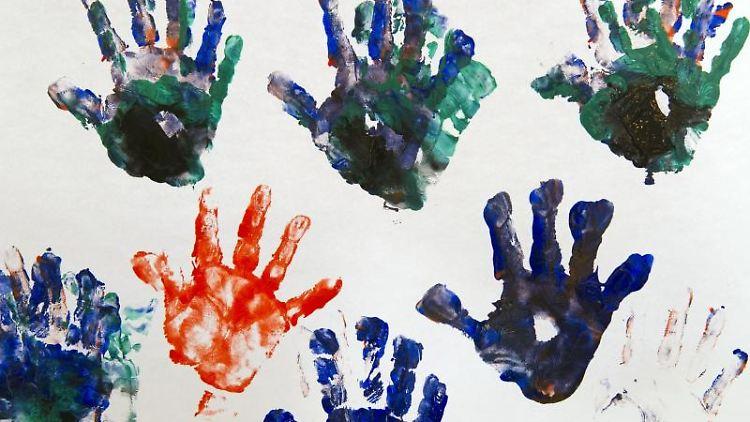 Bunte Handabdrücke eines Dreijährigen sind auf einem weißem Blatt Papier zu sehen. Foto:Peter Kneffel/Archivbild