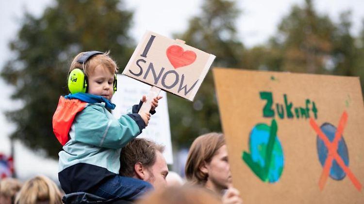 Ein Junge sitzt bei einer Demonstration auf den Schultern seines Vaters. Foto:Christian Charisius