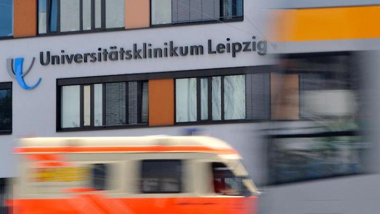 Autos und Straßenbahnen fahren vor dem Universitätsklinikum in Leipzig vorüber. Foto: Hendrik Schmidt/Archivbild