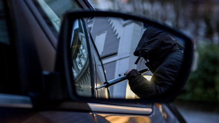 Ein Mann versucht eine Autotür mit einer Metallstange aufzubrechen. Foto: Axel Heimken/Archivbild
