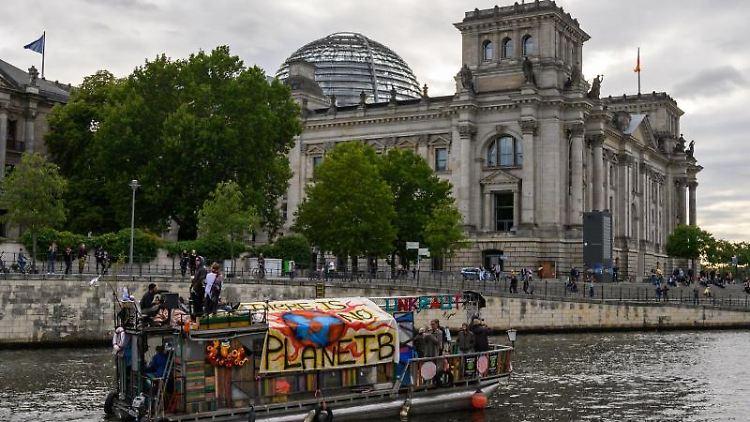 Ein Boot fährt auf der Spree vor dem Reichstag mit einem Banner mit der Aufschrift