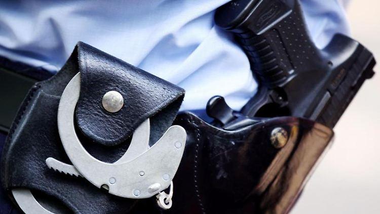 Ein Polizist mit Handschellen und Pistole am Gürtel. Foto: Oliver Berg/Archiv