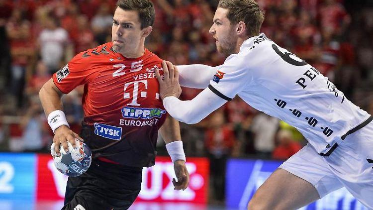 Rasmus Lauge Schmidt (l.) von Telekom Veszprem geht mit dem Ball an Harald Reinkind vom THW Kiel vorbei. Foto: Boglarka Bodnar/MTI