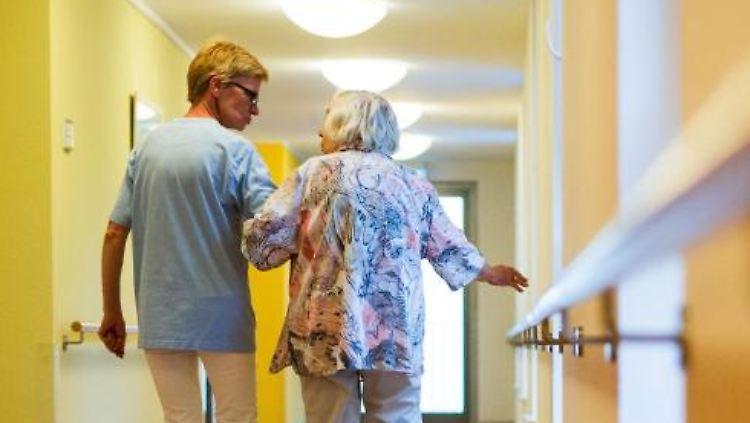 Eine Pflegerin geht in einem Pflegeheim mit einer älteren Dame über einen Korridor. Foto: C. Schmidt/Archivbild