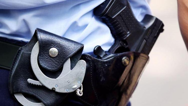 Ein Polizist trägt Handschellen und eine Pistole am Gürtel. Foto: Oliver Berg/Archivbild