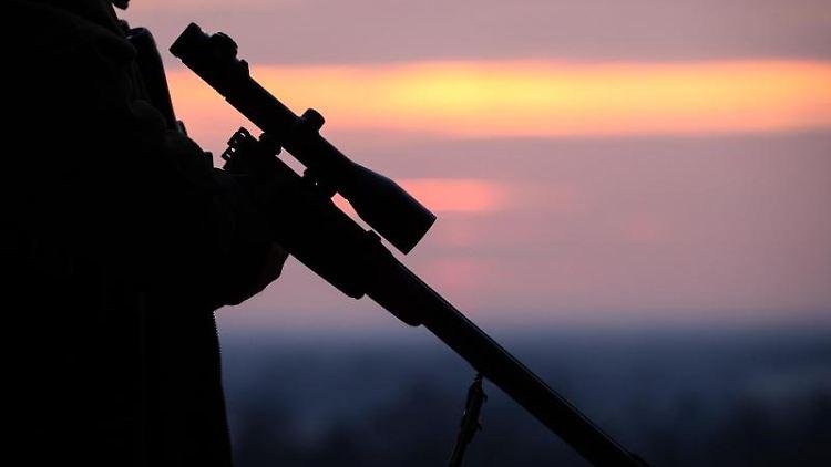 Ein Jäger mit Gewehr in der Abenddämmerung. Foto: Friso Gentsch/Archivbild
