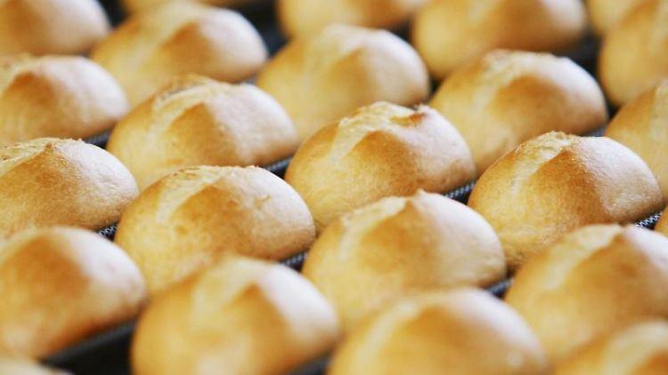 Brötchen kommen auf dem Fließband einer Großbäckerei aus dem Ofen. Foto: Achim Scheidemann/Archivbild