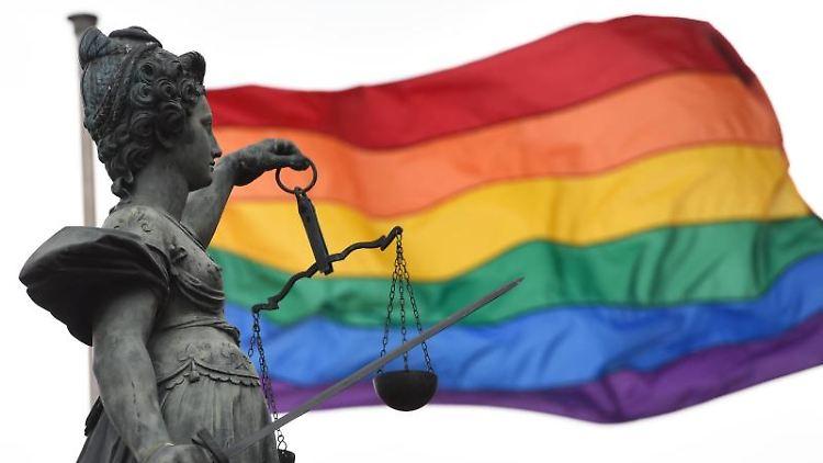Eine Regenbogenfahne weht hinter der Bronzestatue der römischen Göttin der Gerechtigkeit, Justitia, die mit einer Waage und einem Richtschwert in der Hand auf dem Gerechtigkeitsbrunnen des Römerbergs steht.Foto:Arne Dedert/Archiv