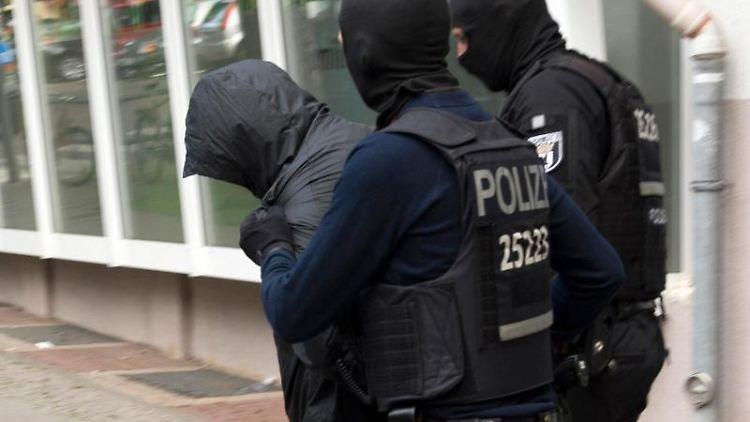 Zwei Polizeibeamte führen einen Mann ab. Foto: Paul Zinken