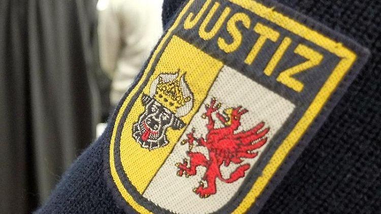 Ein Justizbeamter steht im Sitzungssaal im Landgericht Rostock. Foto: Marcus Brandt/dpa
