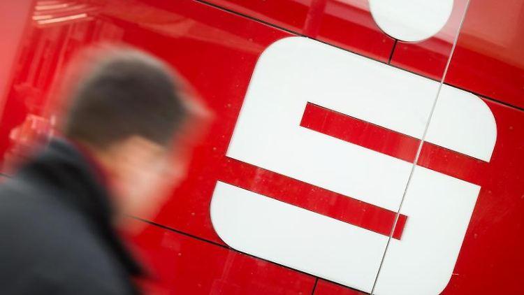 Ein Mann geht an einer Filiale der Sparkasse vorbei. Foto: Julian Stratenschulte/dpa