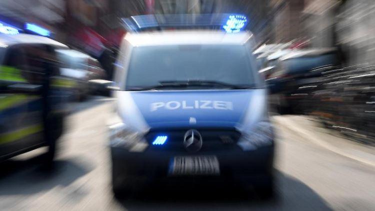 Ein Polizeiwagen mit eingeschalteten Blauchlicht fährt über eine Straße. F. Foto: Carsten Rehder/dpa