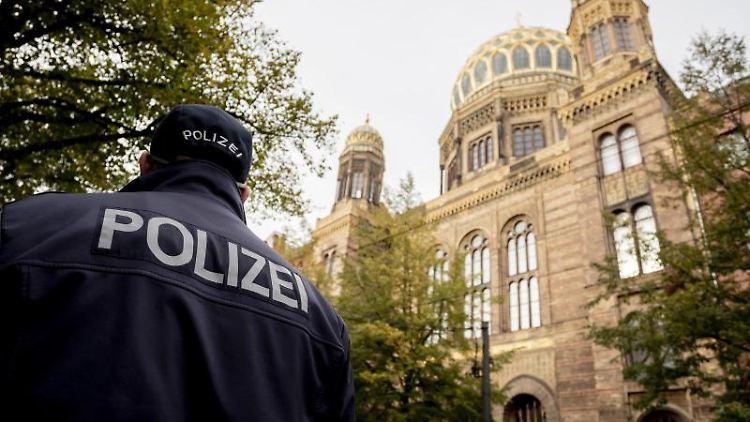 Ein Polizeibeamter läuft vor der Neuen Synagoge Berlin. Foto: Christoph Soeder/dpa