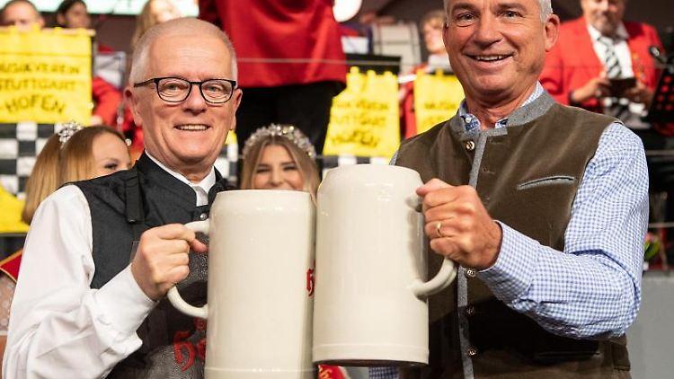 Fritz Kuhn (Die Grünen, l.) und Thomas Strobl (CDU) stoßen mit dem ersten Bier an. F. Foto: Sebastian Gollnow/dpa