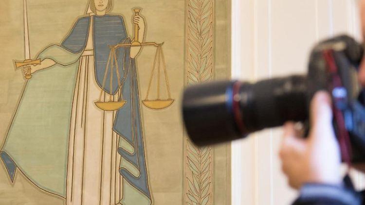 Ein Fotograf vor dem Bild der Justitia. Foto: Friso Gentsch/dpa